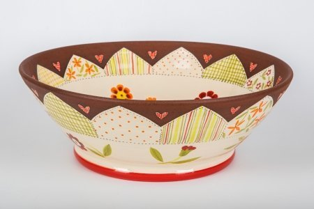 A photo of a white glossy terracotta ceramic bowl, taken from the side, hand decorated with a white glossy centre with white glossy patchwork effect and flowers in the centre and matt terracotta coloured patchwork sections