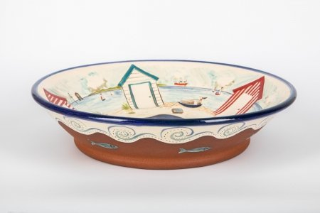 A photo of a matt terracotta ceramic bowl, taken from the side, hand decorated with a white glossy centre with white glossy wavy effect and a seascape in the centre