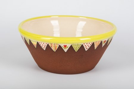 A photo of a matt terracotta ceramic bowl, taken from the side, hand decorated with a white glossy centre with a green rim and a red tulip in the centre