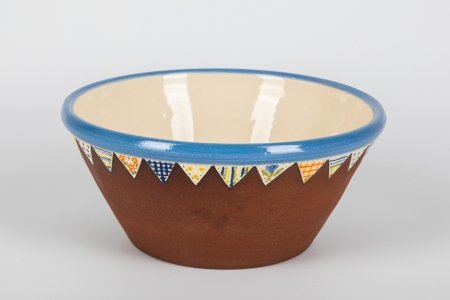 A photo of a matt terracotta ceramic bowl, taken from the side, hand decorated with a white glossy centre with a blue rim and a red tulip in the centre