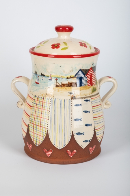 A photo of a decorative ceramic Storage Jar with two-tone/patchwork design with seaside and beach hut decoration on the side