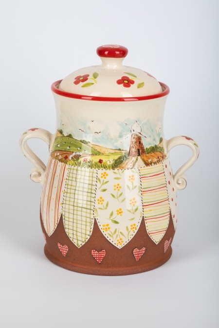 A photo of a decorative ceramic Storage Jar with two-tone/patchwork design with countryside decoration on the side