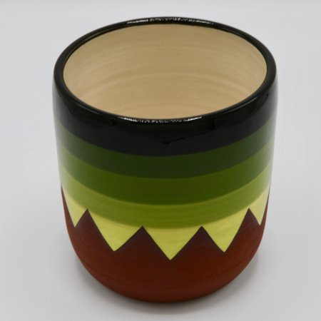 A photo of a decorative ceramic plant pot with stripes and two tone design