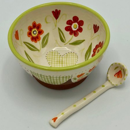 A photo of a hand made terracotta ceramic bowl with a floral design in the centre and a ceramic spoon next to it
