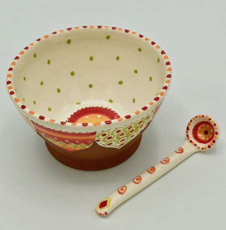 A photo of a hand made terracotta ceramic bowl a ceramic spoon next to it
